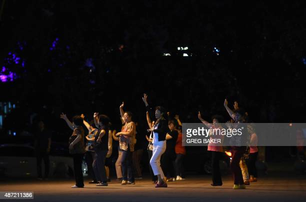 A group of women dance near a residential compound in Beijing on September 7 2015 A spate of noisy disputes between middleaged women and nearby...