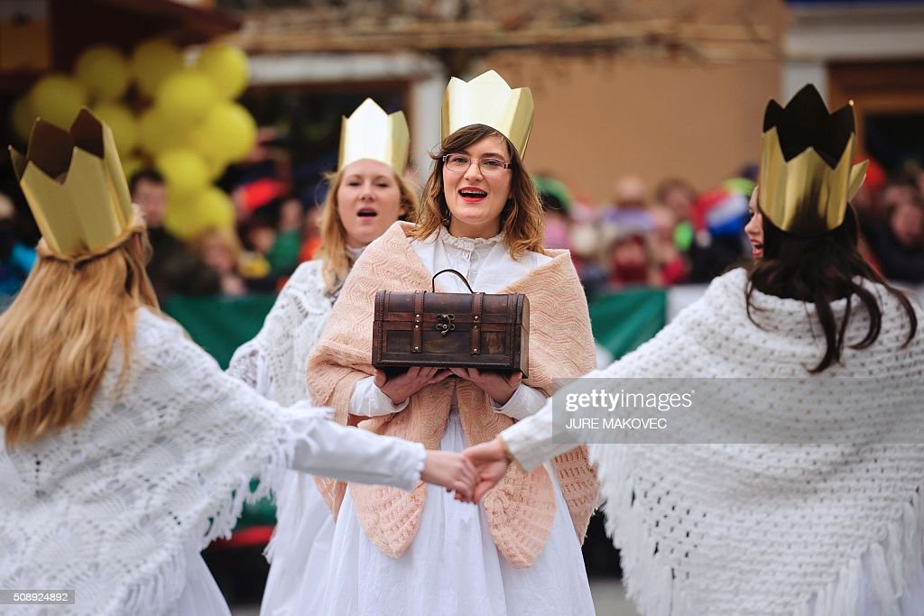 A group of women dressed in traditional Slovenian costume and wearing a crown dance during the Ptuj carnival parade in Ptuj, on February 7, 2016. The Ptuj carnival is the largest in Slovenia and last 11 days. / AFP / JURE MAKOVEC