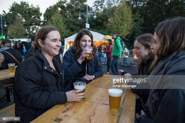 A group of women drink beer at an amusement area set up along 17th of June Street in Tiergraten Park near the Brandenburg Gate on German Unity Day on...