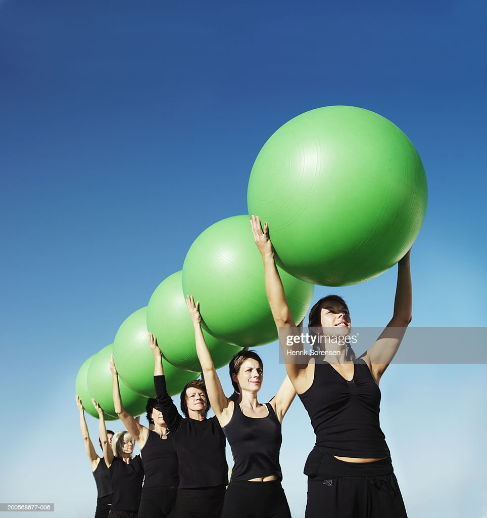 Group of women holding fitness balls over heads, low angle view : Stock Photo