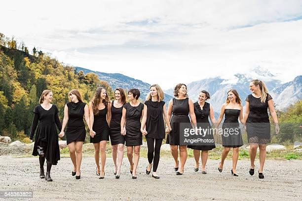 Group of women in black dress walking hand in hand