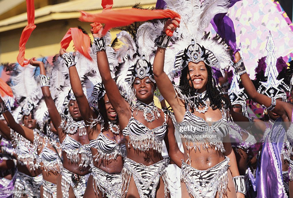 Group of women in carnival costumes with hands in air, portrait