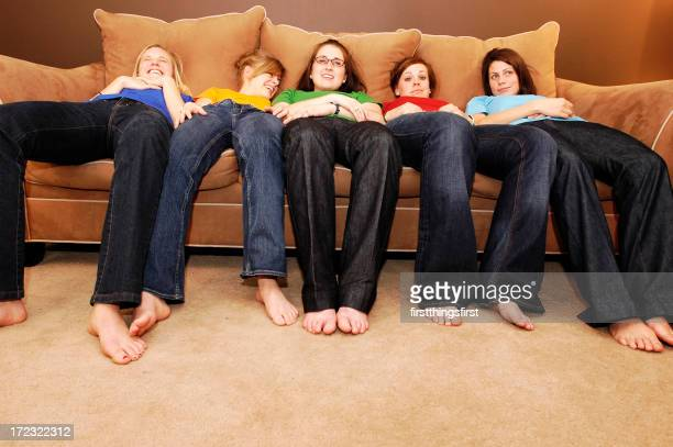 Group of women in colorful shirts lying on giant couch