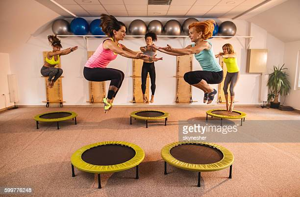 Group of women jumping on trampolines during Pilates exercise class.