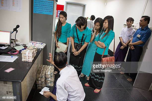 A group of women make a withdrawal at the KBZ Bank main office on October 8 2015 in Yangon Burma In Burma the most widely deposited bank note is...