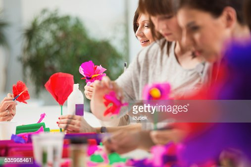 Group of women making paper flowers : Stock Photo