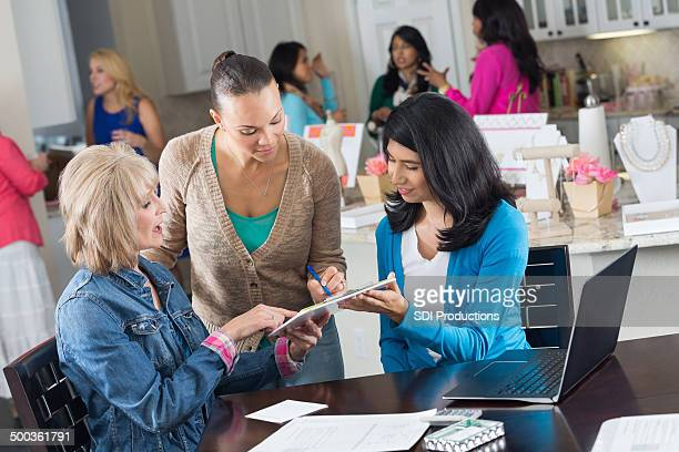 Group of women ordering jewelry at home sales party