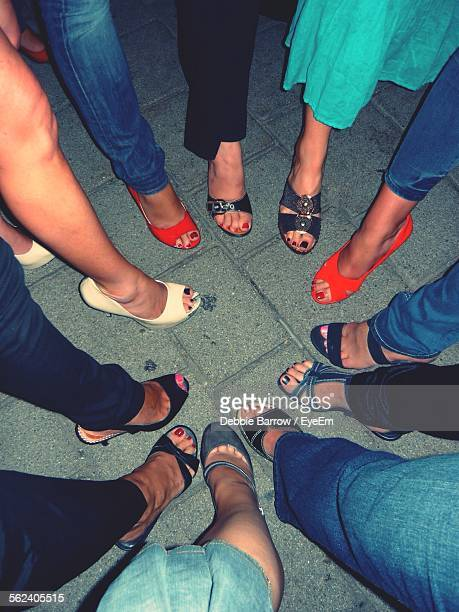 Group Of Women Posing With Their Footwear In Circle