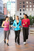 Group Of Women Power Walking On Urban Street Smiling To Each Other