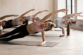 Group of young diverse sporty people doing yoga Vasisthasana pose, Side Plank exercise, working out, indoor close up, female students training at sport club or studio. Well being, wellness concept
