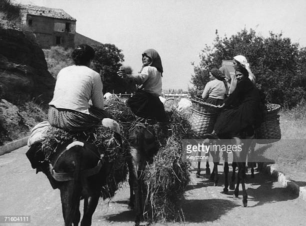 A group of women riding donkeys on a road near San Marcellino south of Naples Italy circa 1955