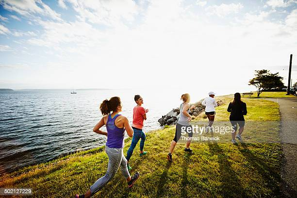 Group of women running together on grass rear view