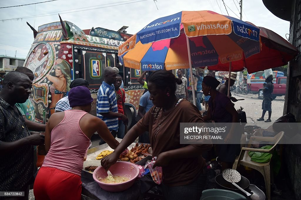 A group of women sell food in front of the stop of the Tap Tap, public transportation vehicle, in Port-au-Prince on May 27, 2016. / AFP / HECTOR