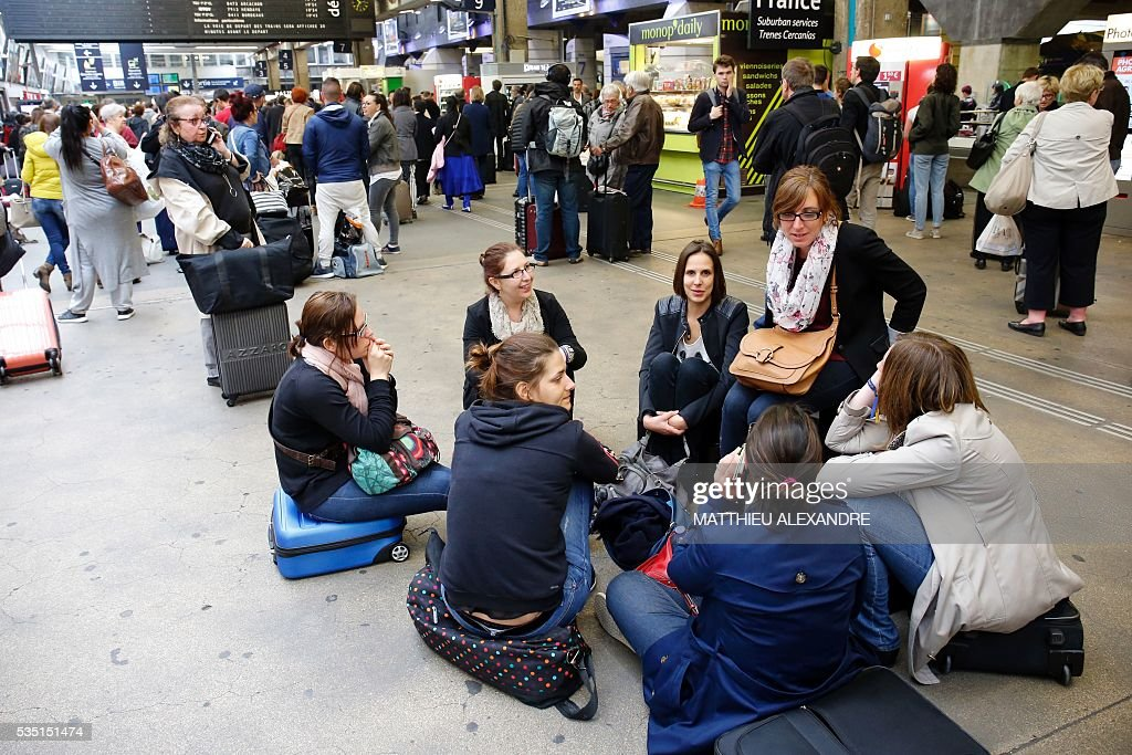 A group of women sit on the ground as they look at the display panel indicating delayed trains as the train traffic was suspended since this morning at the start and towards the Paris-Montparnasse rail station, due to a failure of traffic management system for the moment unexplained, according to France's national state-owned railway company SNCF, on May 29, 2016 in Paris.