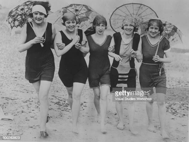 A group of women walk along the beach wearing bathing suits and carrying umbrellas Skegness England early to mid 20th century Despite the cold and...