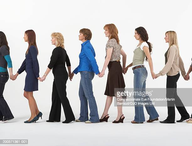 Group of women walking in row holding hands, side view