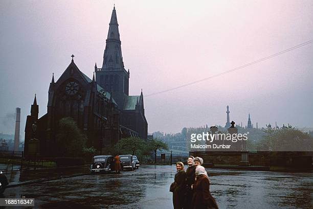 A group of women walking through Cathedral Square in front of Glasgow Cathedral Glasgow 1955 The Knox Statue on top of the Glasgow Necropolis can be...