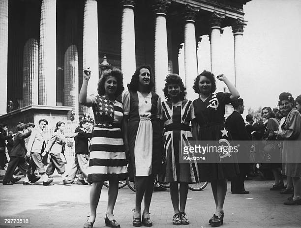 A group of women wearing dresses representing flags of the Allied powers outside the Eglise de la Madeleine on VE Day in Paris 8th May 1945