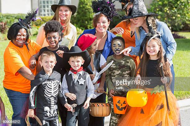 Group of women with children in halloween costumes