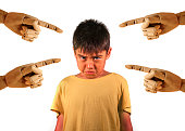group of wood hands pointing finger to young sad and stressed schoolboy victim of abuse and bullying isolated on white background in kid harassed and bullied at school concept