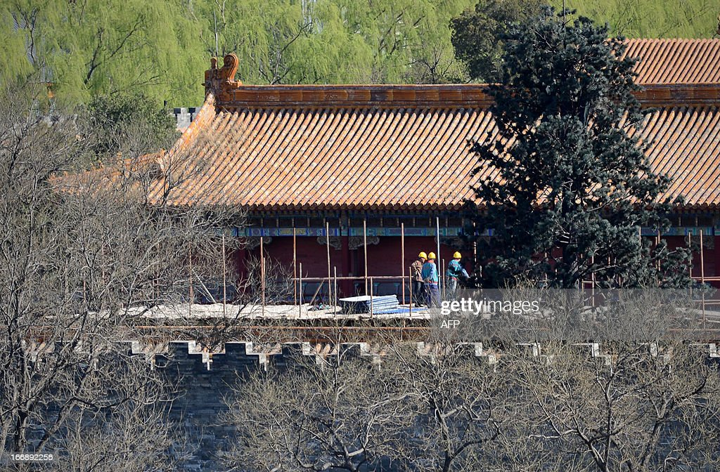 A group of workers arrive at the Forbidden City in Beijing on April 18, 2013. The historic 700 year old park includes a 45 metre man-made hill which was built to provide a favourable Feng Shui environment for the nearby Forbidden City.