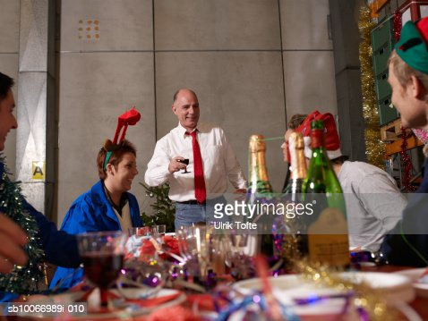 Group of workers celebrating at charismas table in warehouse : Stock Photo