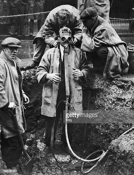 A group of workers don gas masks in order to investigate a gas leak in St Paul's Churchyard 9th June 1931