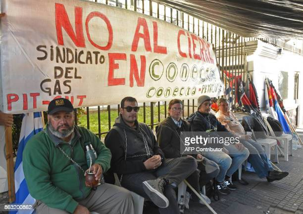 A group of workers from the Uruguayan gas union chain themselves to the Brazilian embassy building in Montevideo to protest on October 19 2017...