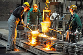 Group of workers in a foundry at the melting furnace - production of steel castings in an industrial company