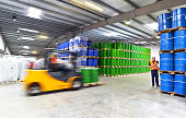 group of workers in the logistics industry work in a warehouse with chemicals - lifting truck