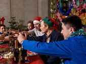 Group of workers sitting at christmas table in warehouse toasting with wine glasses