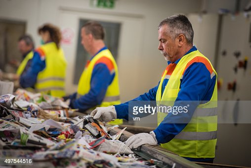Group of workers sorting papers at recycling plant