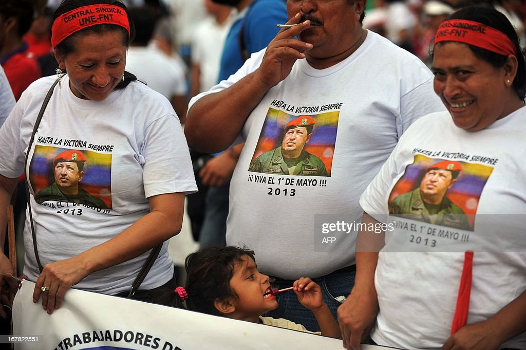 A group of workers with t-shirts bearing the image of the late Venezuelan president Hugo Chavez participate in an event organized by the National Workers Front FNT to celebrate International Workers Day, officially celebrated on May 1, in Managua, April 30, 2013. AFP PHOTO/Hector RETAMAL