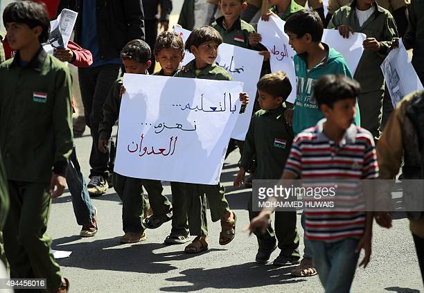 A group of Yemeni children hold a poster reading in Arabic 'education defeats agression' as they gather in front of the United Nations office during...
