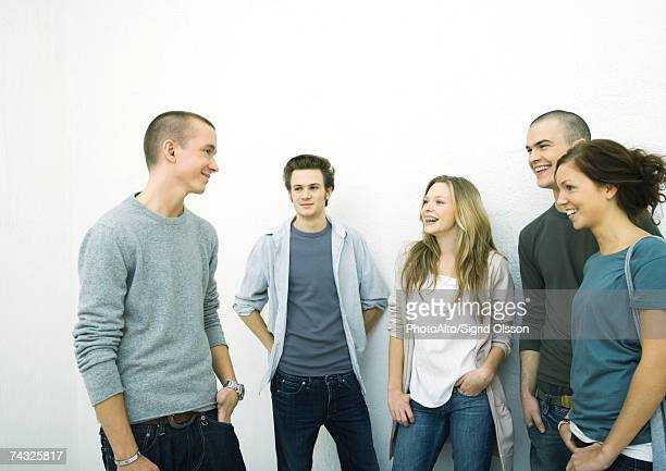 Group of young adult and teenage friends standing together, white background