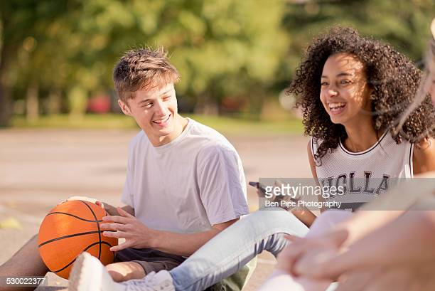 Group of young adult basketball players sitting chatting