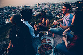 Group of young adult friends having picnic with pizza at sunset and watching the city