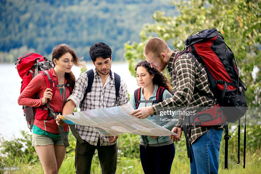 Group of young adult friends reading a trailmap