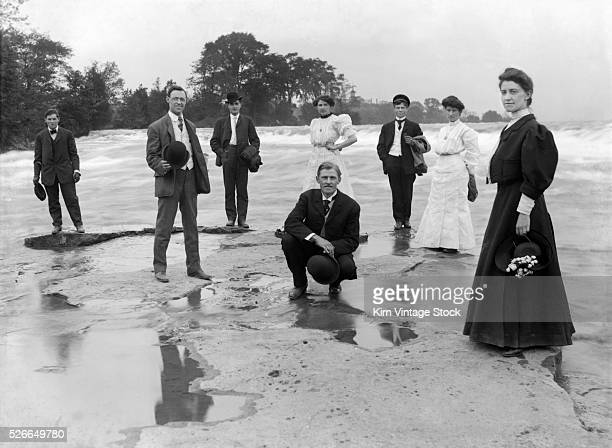 A group of young adults are strategically positioned for a formal beach portrait at the beginning of the 20th century