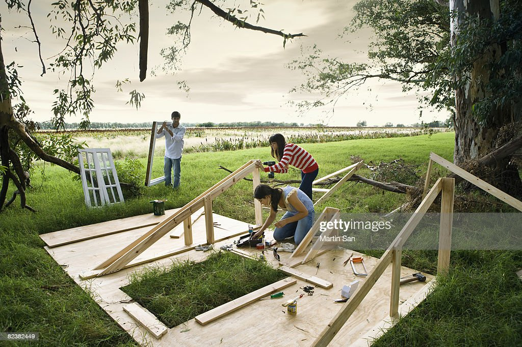 Group of young adults building wall : Stock Photo