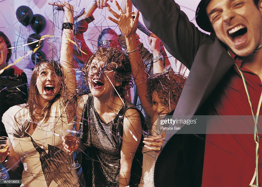 Group of Young Adults Cheering Under Streamers at a Party : Stock Photo