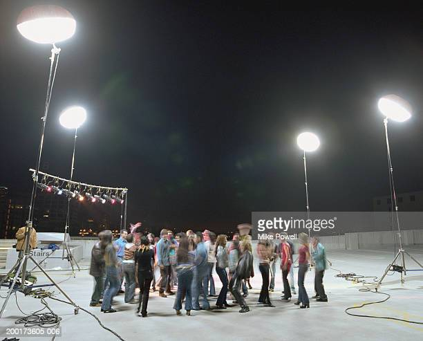Group of young adults dancing at rooftop set (blurred motion)