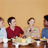 Group of young adults eating dessert and drinking wine at dinner party