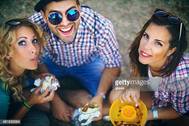 Group of young adults eating outdoors.