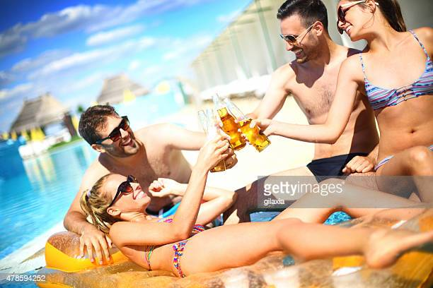 Group of young adults having beers at swimming pool.