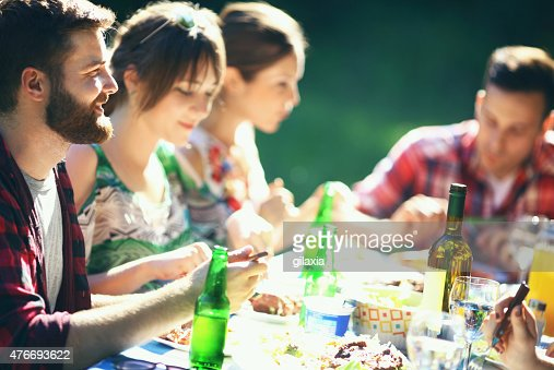 Group of young adults having lunch outdoors.