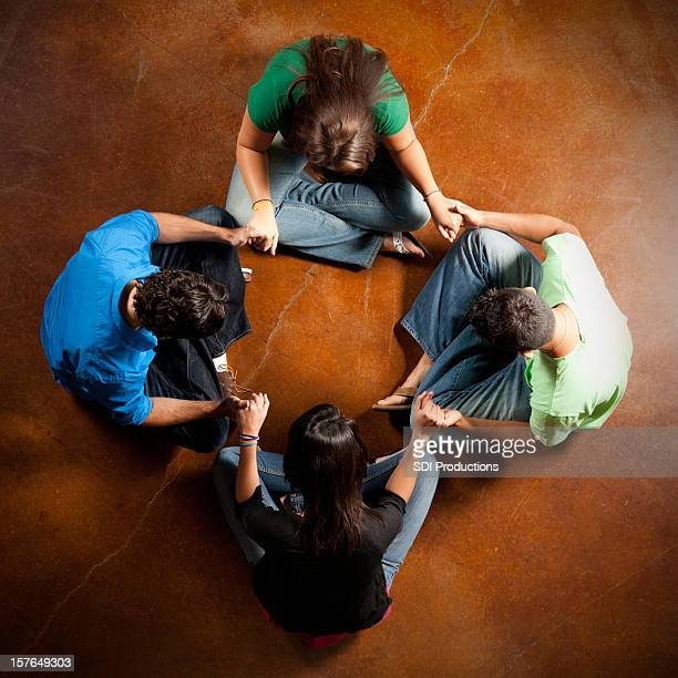 Gruppe von jungen Erwachsenen, die Hände und Beten zusammen