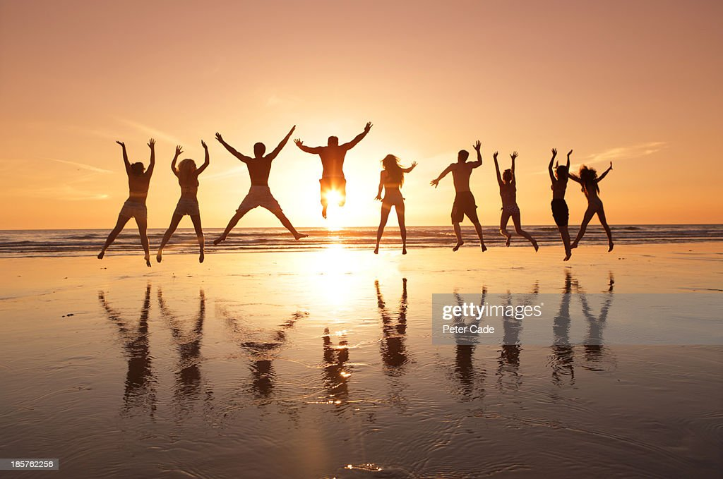 Group of young adults jumping on beach at sunset : Stock Photo