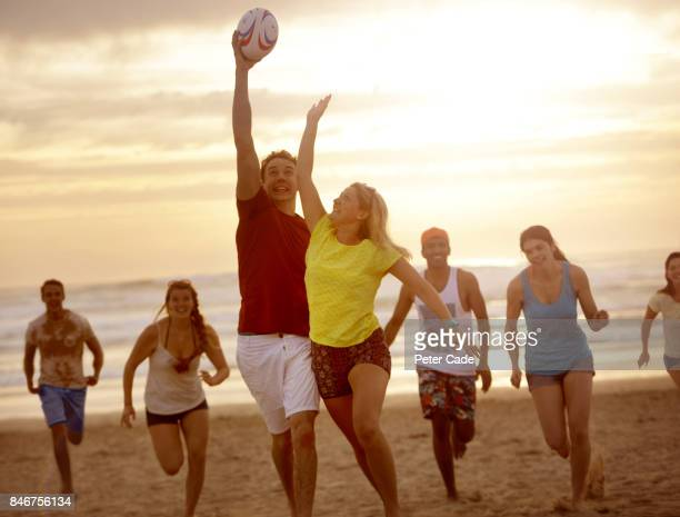 Group of young adults on beach playing with rugby ball