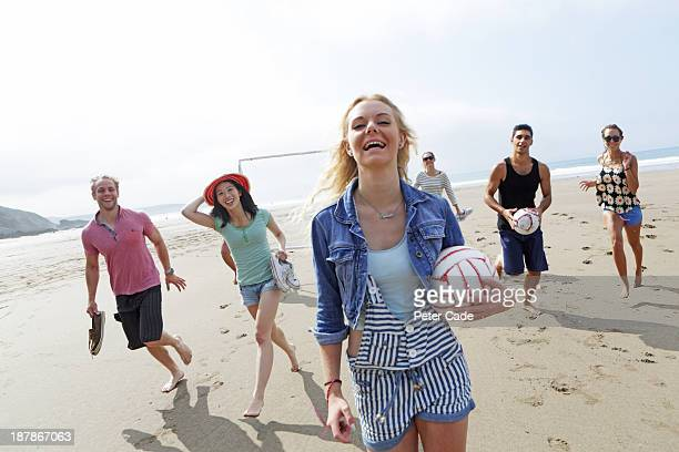 Group of young adults on beach with ball and goal